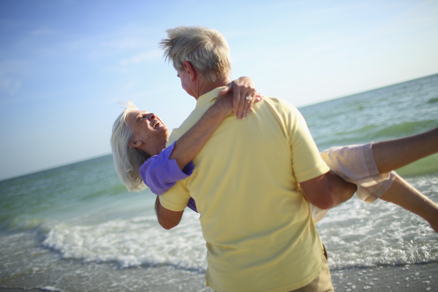 Senior man carrying his wife on the beach